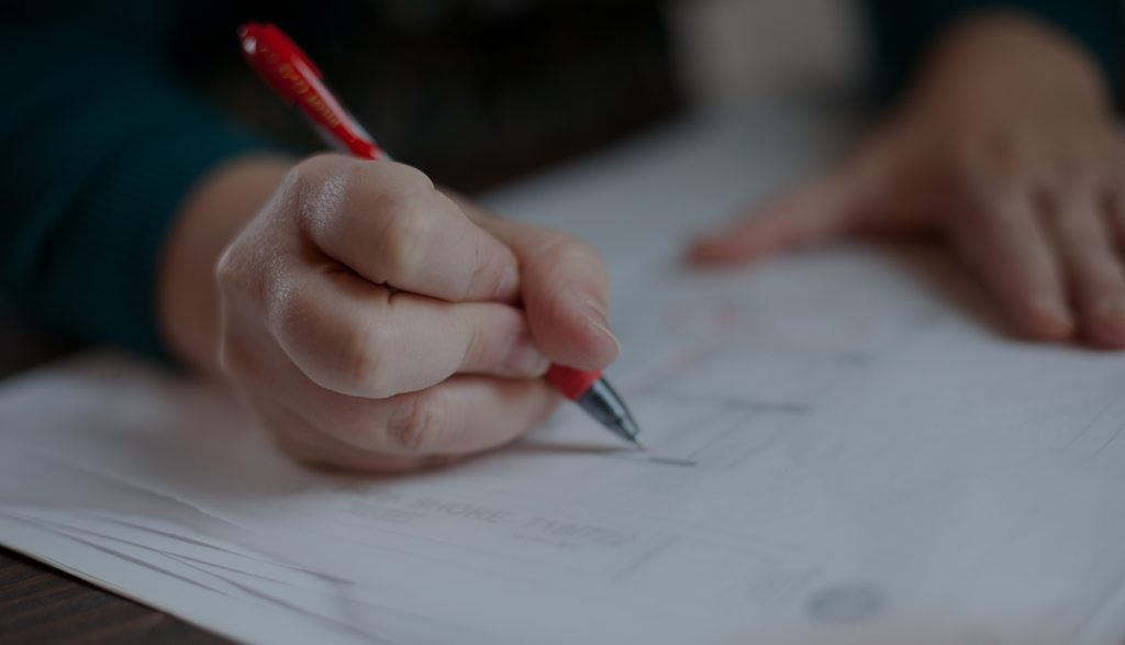 Hand holding pen, writing on construction documents
