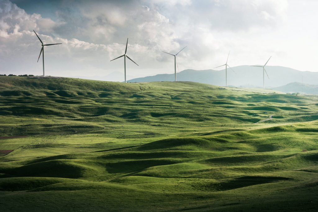 Green design and sustainability: wind farms on grassy hills.